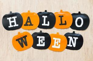 Halloween decorations, black and orange pumpkins on a wooden background photo