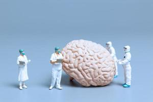Médicos en miniatura que controlan y analizan un cerebro en busca de signos de la enfermedad de alzheimer y la demencia, el concepto de ciencia y medicina foto