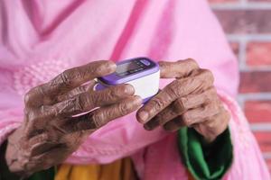 Mano de mujer mayor con oxímetro de pulso foto