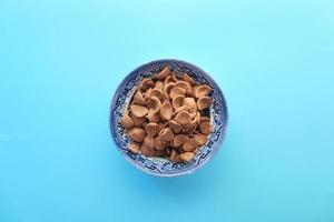 Top view of chocolate corn flakes in a bowl on blue background photo