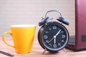 Despertador y taza de café en la mesa foto