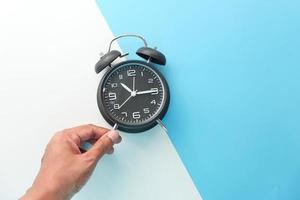 Old alarm clock on blue and white background photo