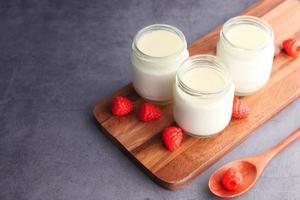 Cerca de yogur fresco en tazones sobre fondo de madera