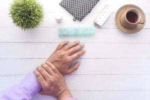 Las manos del hombre sobre la mesa con medicina y café.