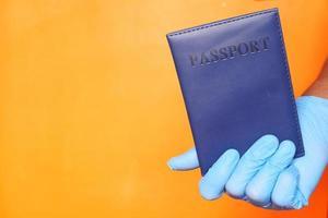 Mano en guantes quirúrgicos azules con pasaporte foto