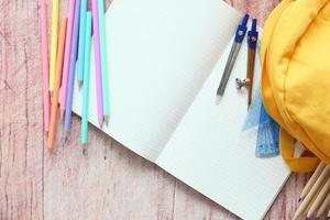 Top view of yellow backpack with colorful stationery on table photo