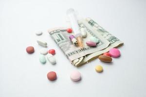concepto de costo de atención médica con dólares estadounidenses, jeringas y píldoras