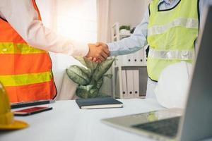 negociación exitosa y concepto de apretón de manos, dos ingenieros o arquitectos se dan la mano foto