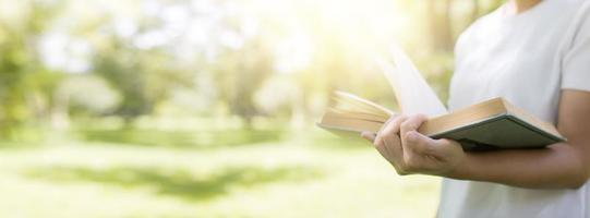 Read and knowledge concept, hand holding book on soft green park banner background photo