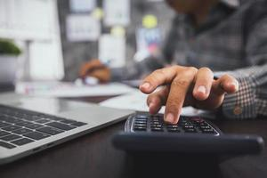 Close up hand of businessman pressing on calculator photo