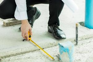 El inspector usa cinta métrica para verificar la medida del ancho del drenaje en el edificio. foto