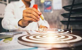 Close-up hand of businessman holding dart on target with financial graph photo