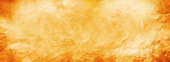 Yellow and orange grunge cement texture wall in summer banner background photo