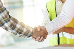 Ingenieros de primer plano un apretón de manos con el contratista de obras en el sitio de construcción foto