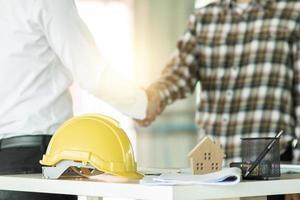ingeniero se da la mano con el contratista de la construcción foto