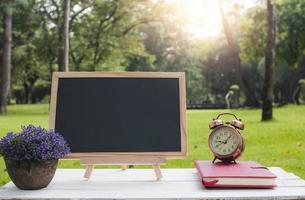 Empty small black board on table with notebook photo