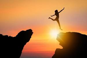 Silhouette of person jumping over rock mountain successfully