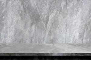 Mesa de cemento gris, piso de concreto y estante para exhibir el producto. foto