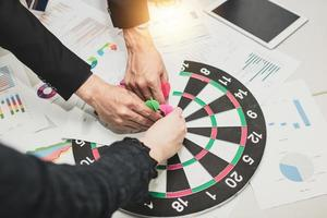 Target and goal concept, business people put dart on board at meeting photo