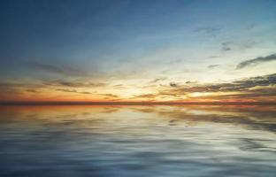 Colorido atardecer nublado sobre cuerpo de agua foto
