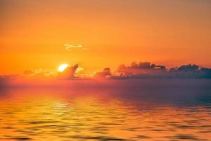 Orange cloudy sunset over body of water