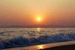 Olas rompiendo en una playa con atardecer nublado naranja sobre las montañas