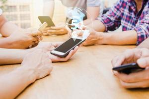 5g internet and technology concept, group of people holding phone on table photo