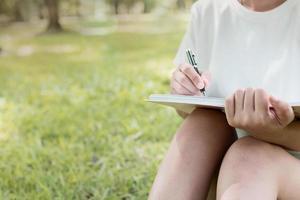 Mano de mujer escribiendo en el cuaderno sobre fondo verde naturaleza foto
