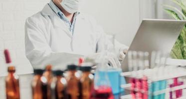 químico o médico investigando y probando medicamentos y encontrando información en una computadora portátil