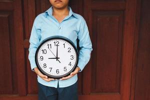 Boy holding a clock