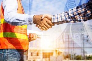 Arquitecto contratista un apretón de manos con el cliente en el sitio de construcción foto