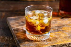 Glass of whiskey on wood