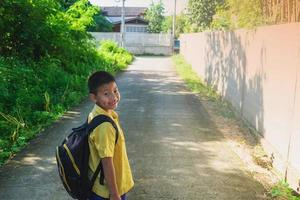 Boy walking with a backpack photo