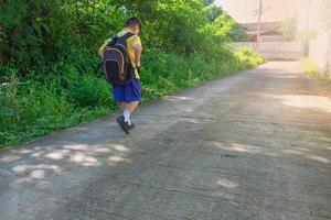 Boy walking outside while wearing a backpack photo