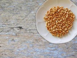 Cacahuetes en una placa blanca sobre un fondo de mesa de madera