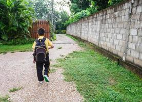Boy walking to school with a backpack photo