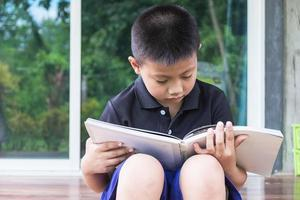 Boy reading outside photo