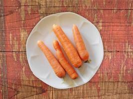 Zanahorias en un plato blanco sobre un fondo de mesa de madera foto