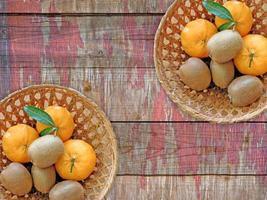 Kiwis y naranjas en dos cestas de mimbre sobre un fondo de mesa de madera foto