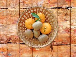 Kiwis y naranjas en una cesta de mimbre sobre un fondo de mesa de madera foto