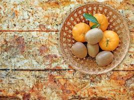 Kiwis y naranjas en una canasta de mimbre sobre una mesa de madera backgroundkiwis y naranjas en una canasta de mimbre sobre un fondo de mesa de madera foto