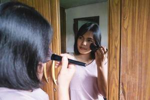 mujer aplicando rubor en un espejo foto