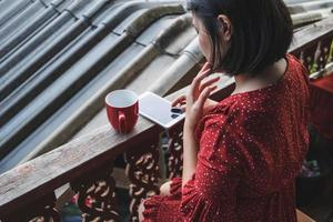Woman sitting with a coffee and phone on a terrace photo