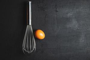 Whisk with an egg on a black background