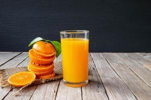 Jugo de naranja y naranja fresco en una mesa de madera foto