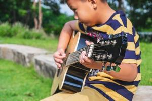 Boy playing a guitar outside photo