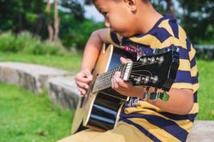 Boy playing a guitar outside