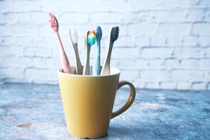 Cepillos de dientes de colores en taza blanca foto