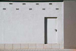 Puerta metálica blanca sobre una pared blanca foto