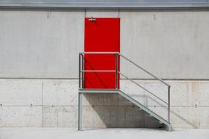 Puerta metálica roja sobre una pared blanca foto